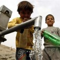 Afghan children prepare to collect water from a water pump in Kabul