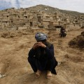 Afghan survivors mourn for their relatives at the site of a landslide at the Argo district in Badakhshan province